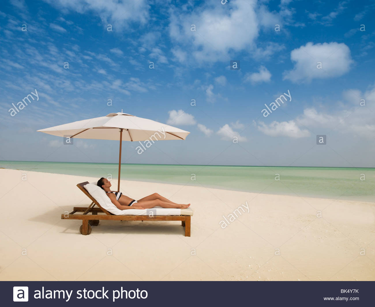 Woman Laying On Lounge Chair Under Beach Umbrella