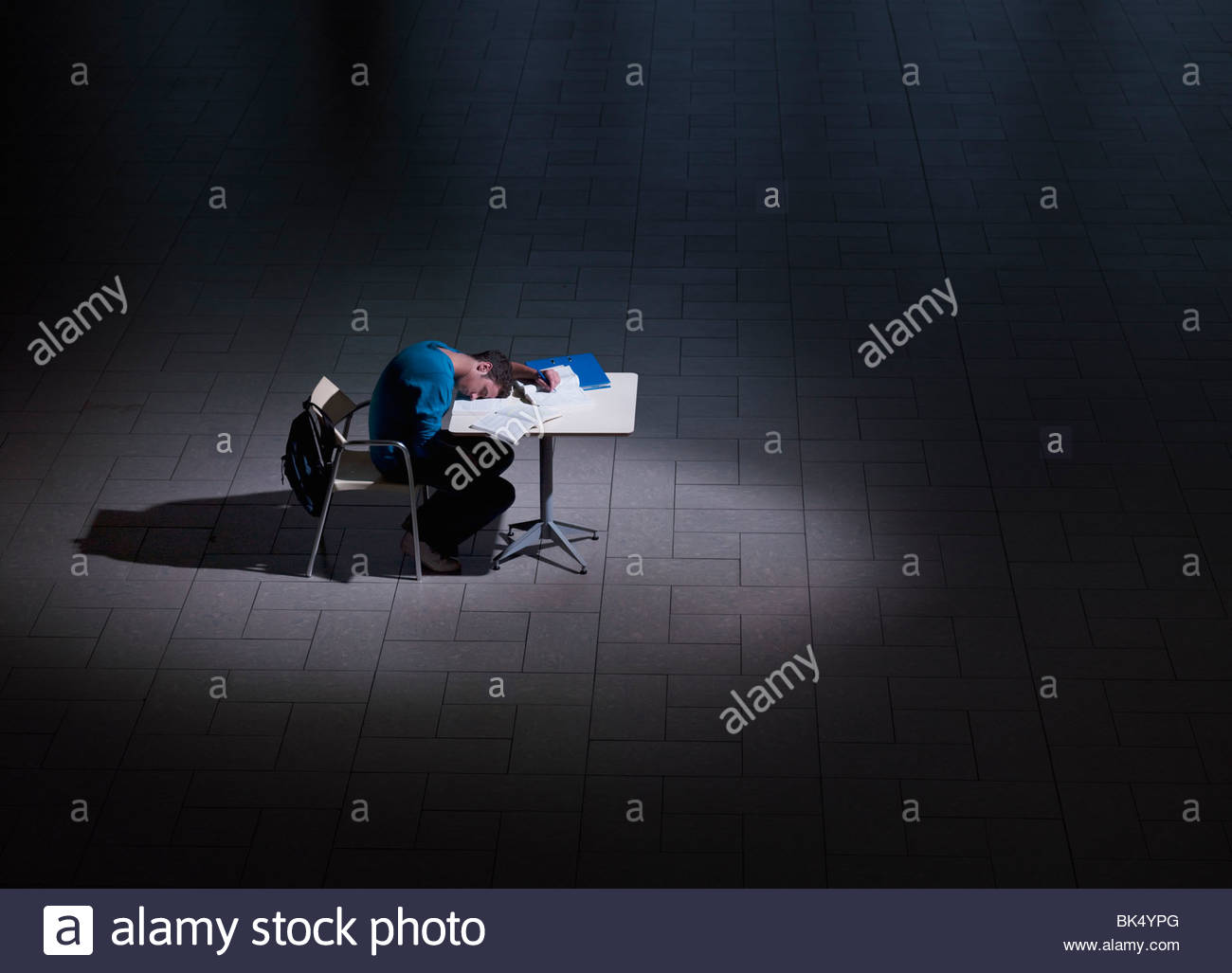 Male student sleeping on desk in darkness - Stock Image