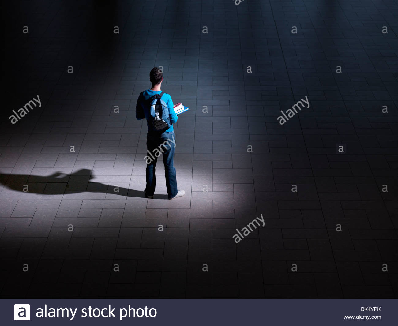 Male student with backpack and books in dark room - Stock Image