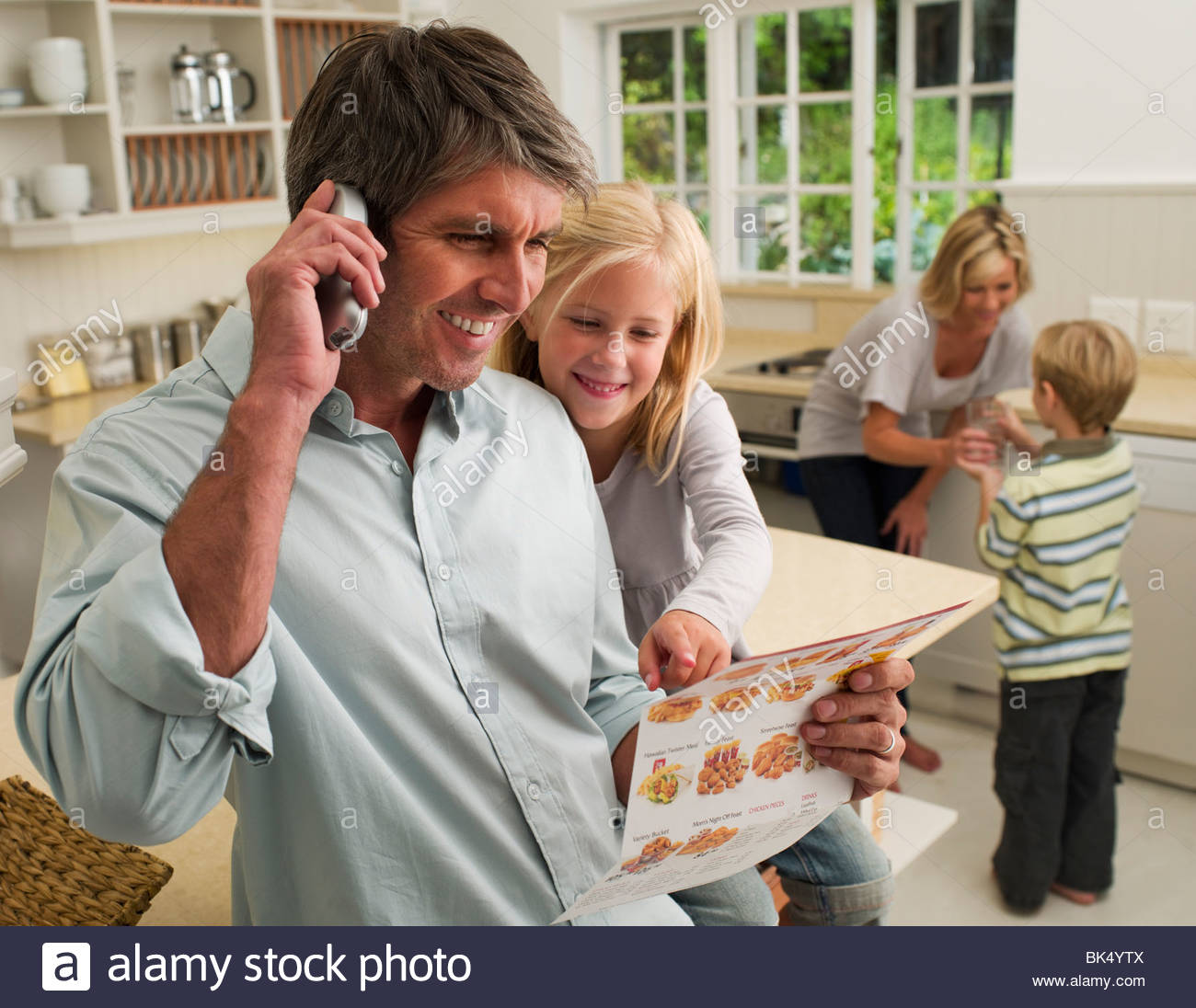Family ordering take out food by telephone in domestic kitchen - Stock Image