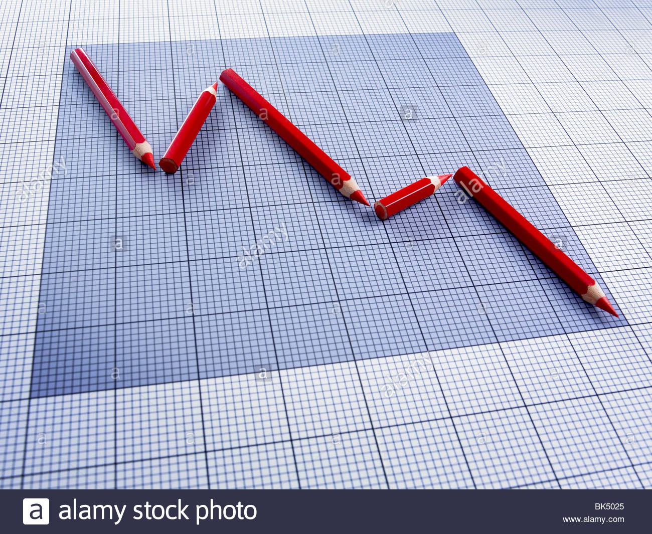 Red pencils forming declining graph - Stock Image