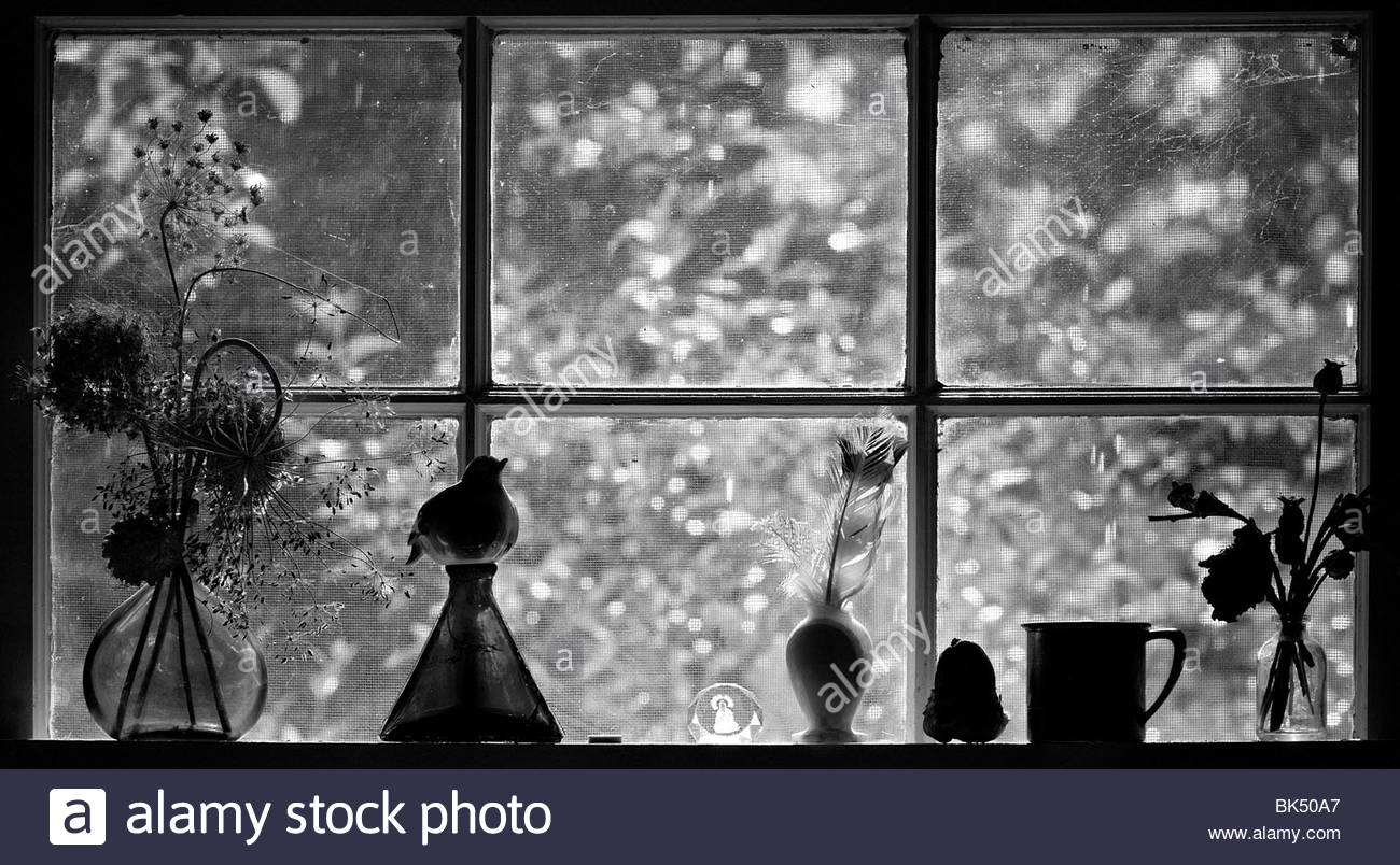 A Kitchen Window with mementos and souvenirs. Warm sunlight coming through the glass. - Stock Image
