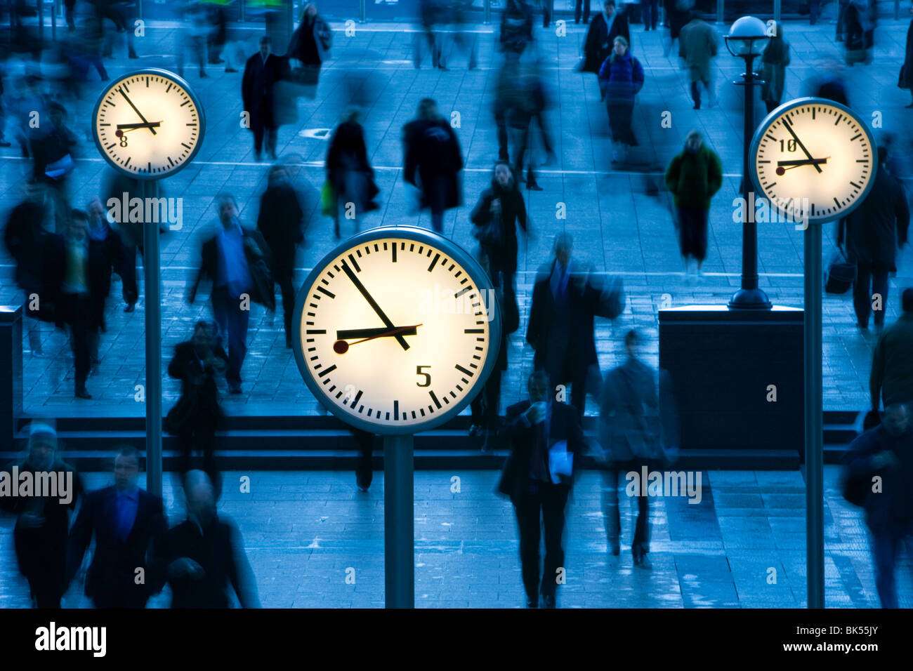 CLOCKS AND MOVING PEOPLE CANARY WHARF LONDON UK - Stock Image