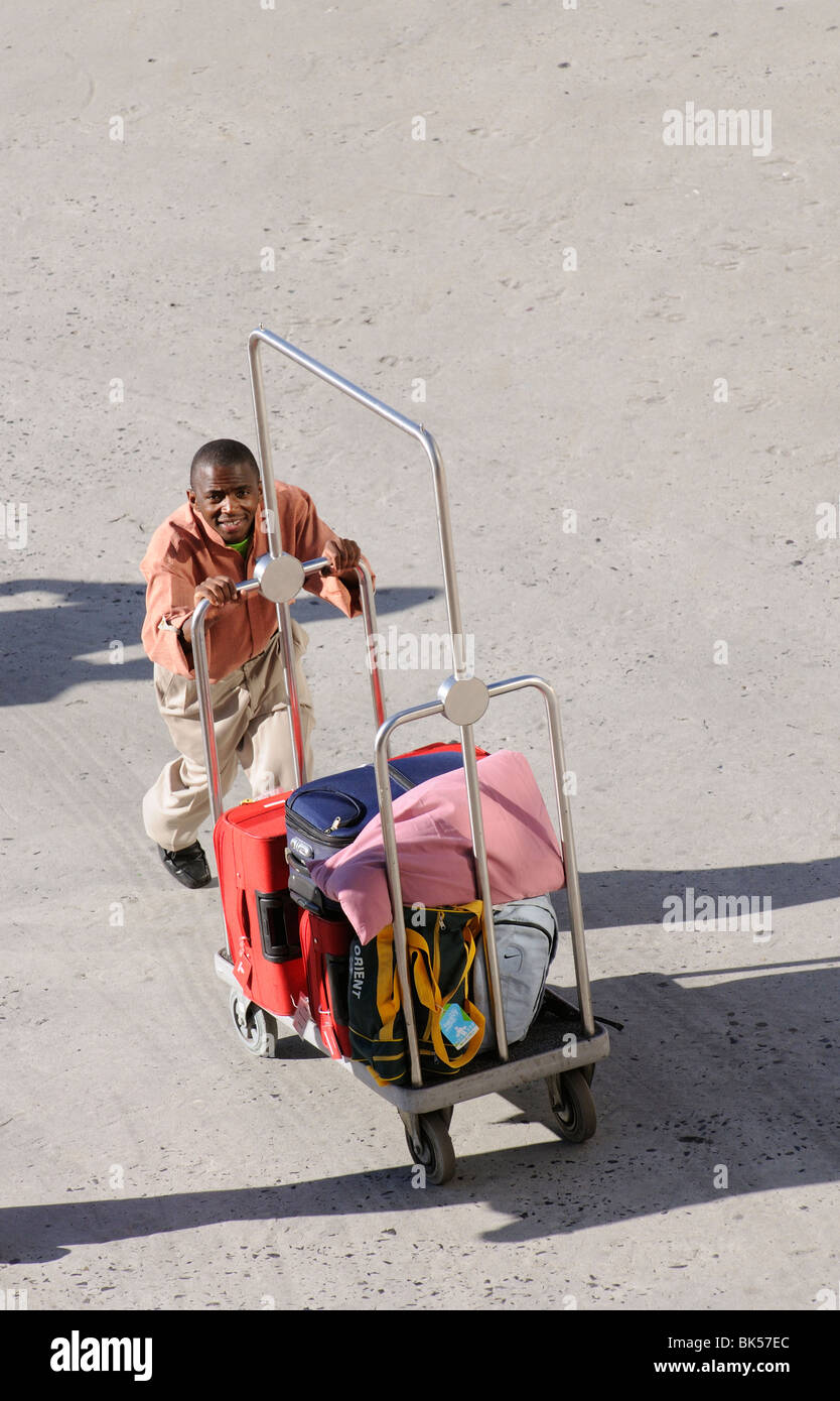 hotel bellboy pushing a guests luggage on his trolley - Stock Image