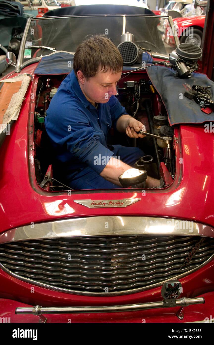 Mechanic working in a classic car restoration workshop ...
