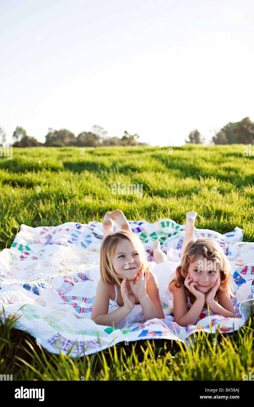 Young girls laying on picnic blanket - Stock Image