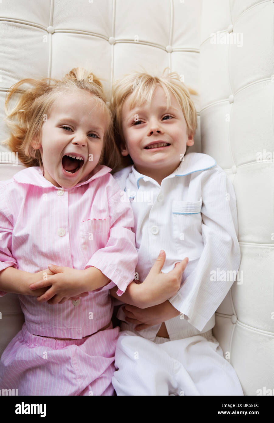 Brother and sister in pajamas on sofa - Stock Image