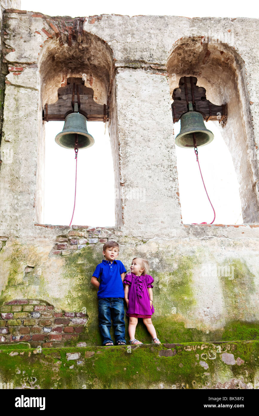 Brother and sister standing below bells - Stock Image