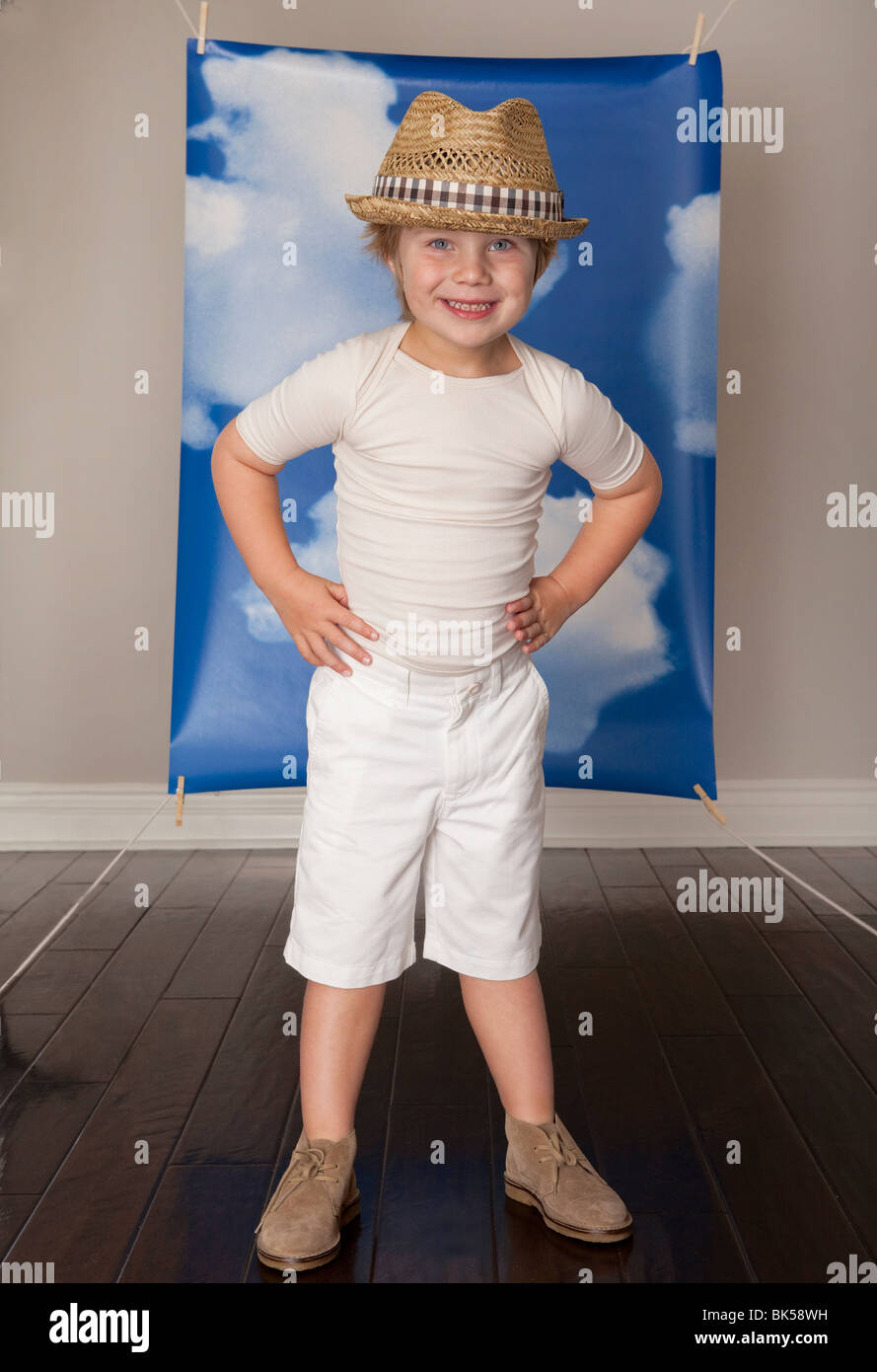 Happy boy in front of blue sky back drop - Stock Image