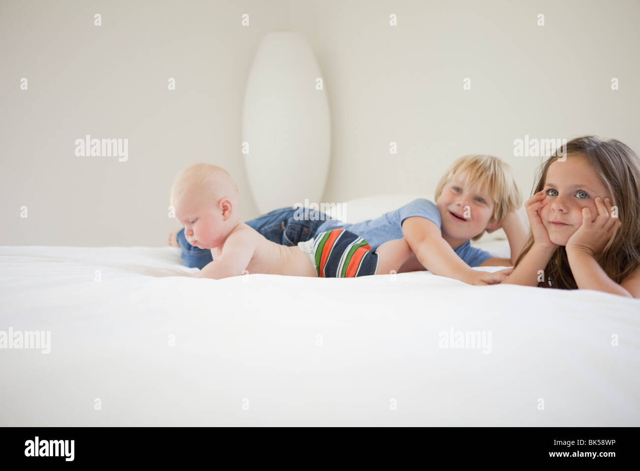 Siblings lounging on white bed - Stock Image