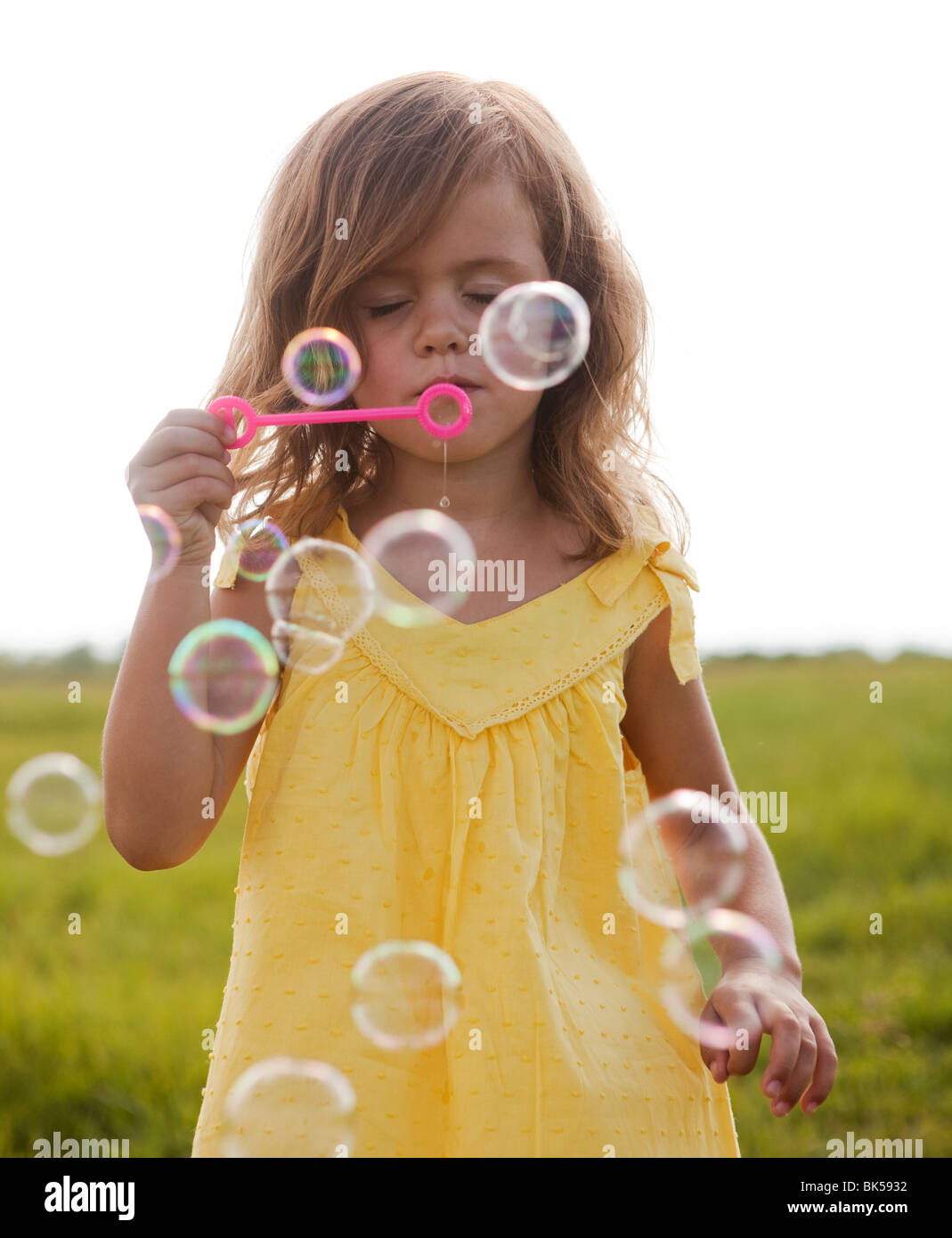 Young girl in yellow sundress blowing bubbles - Stock Image