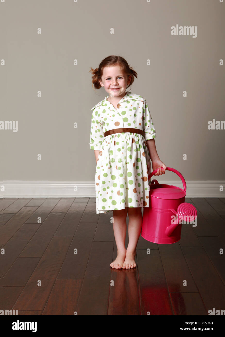 Girl in polka dot dress holding watering can - Stock Image