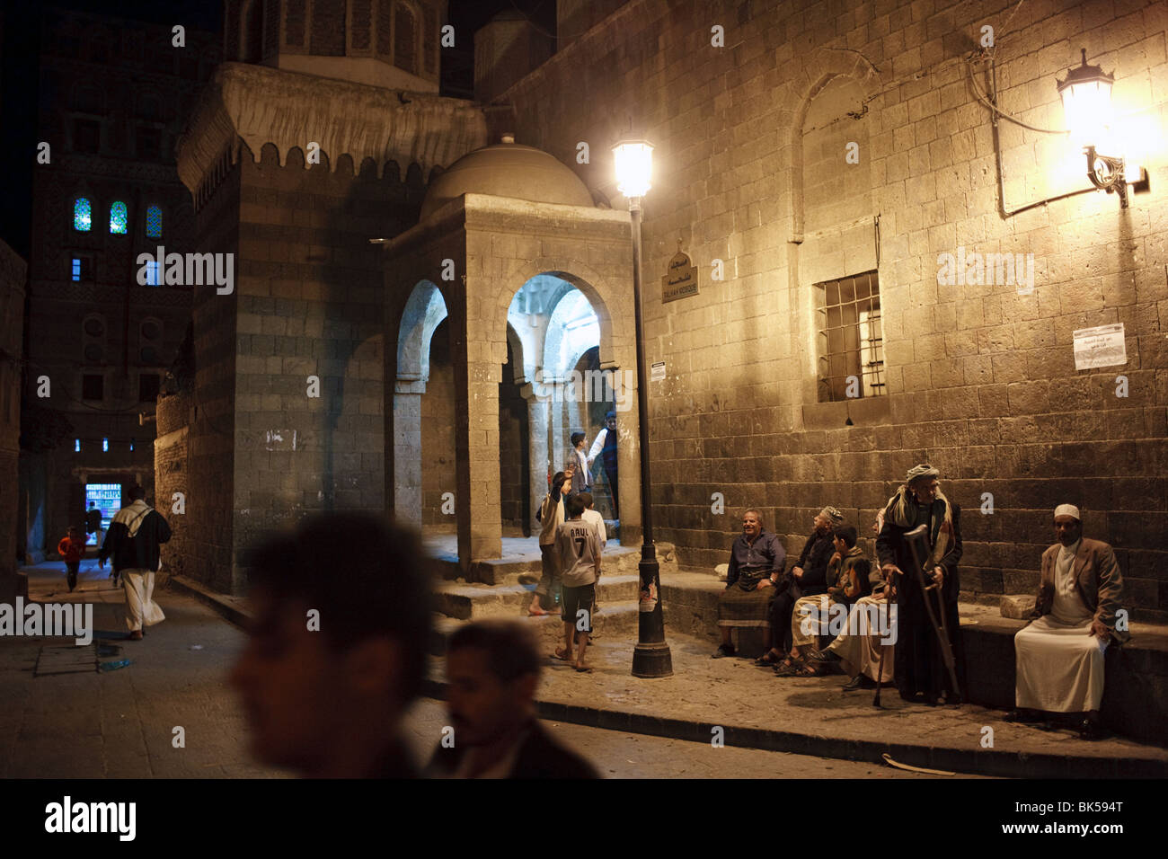people at night outside an old mosque in Sana'a, Yemen - Stock Image