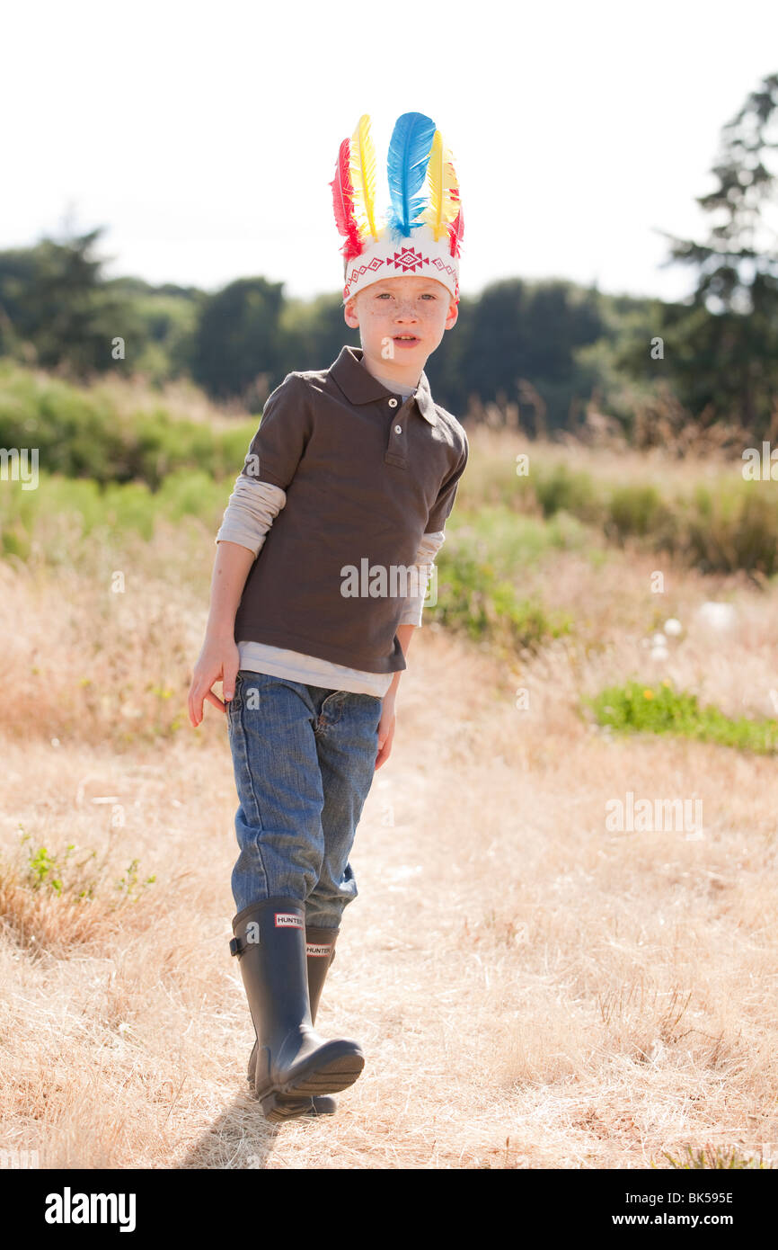 Young boy wearing indian feathers - Stock Image