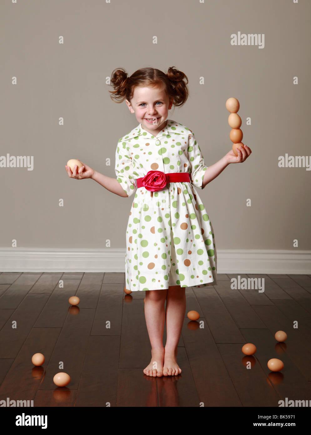 Girl in polka dot dress balancing eggs - Stock Image