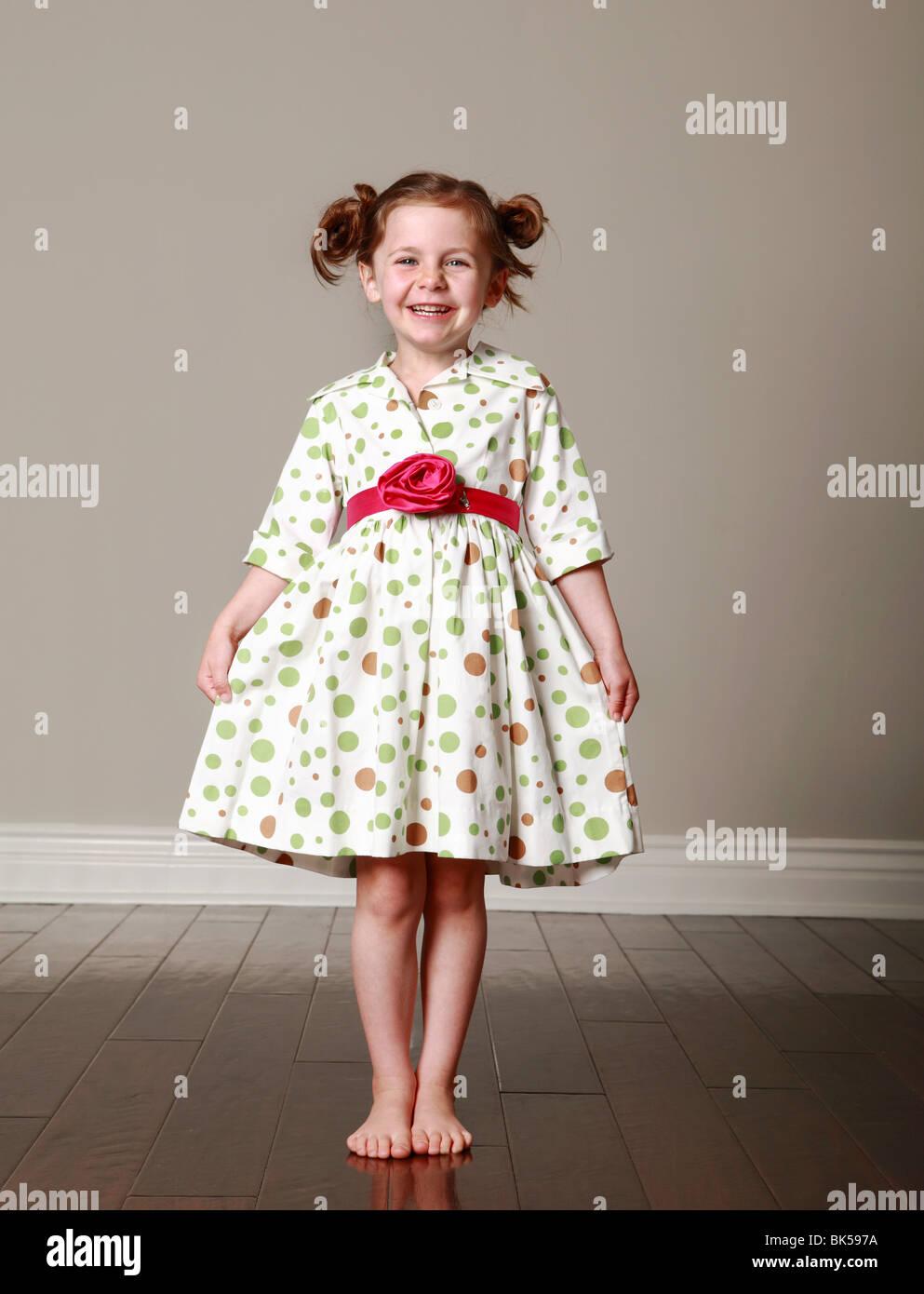 Girl showing off polka dot dress - Stock Image