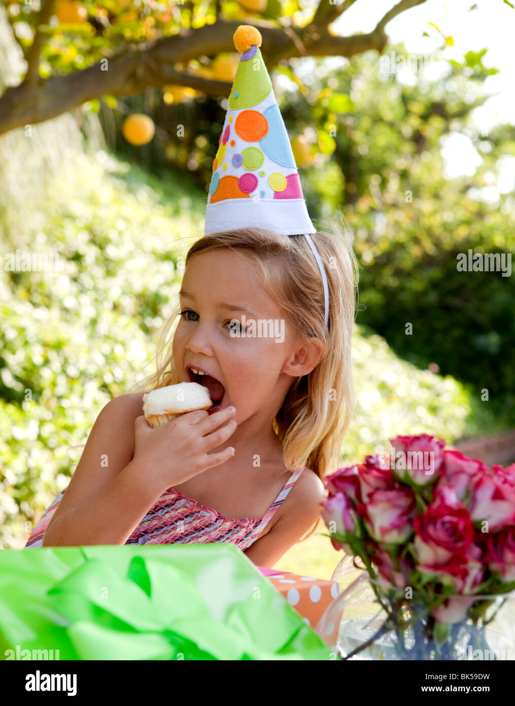 Young girl with party hat eating cupcake - Stock Image