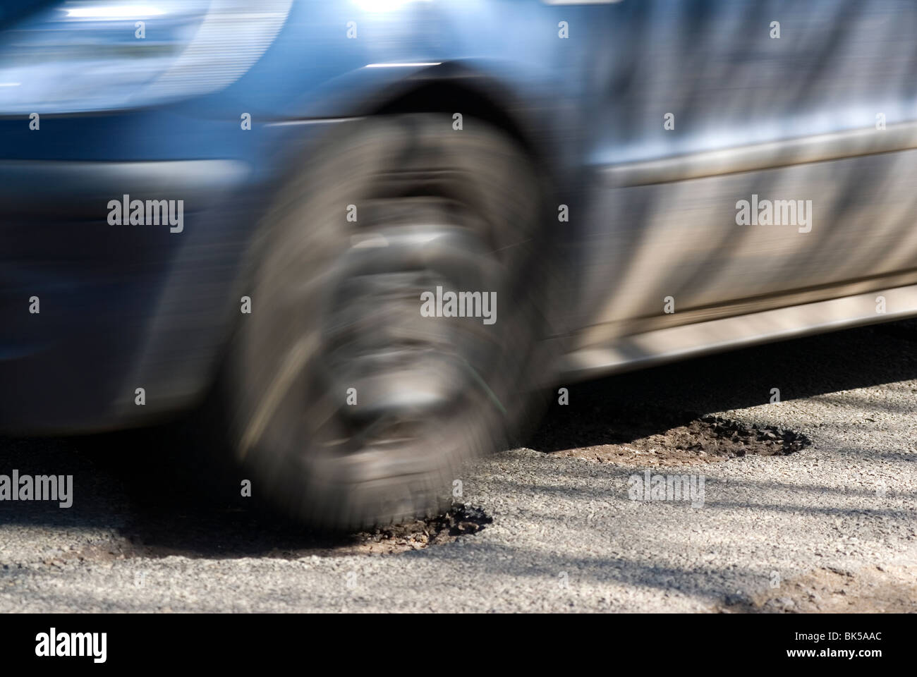 potholes in the middle of the road after a hard winter of snow. Who will pay for these pot holes to be repaired? Stock Photo