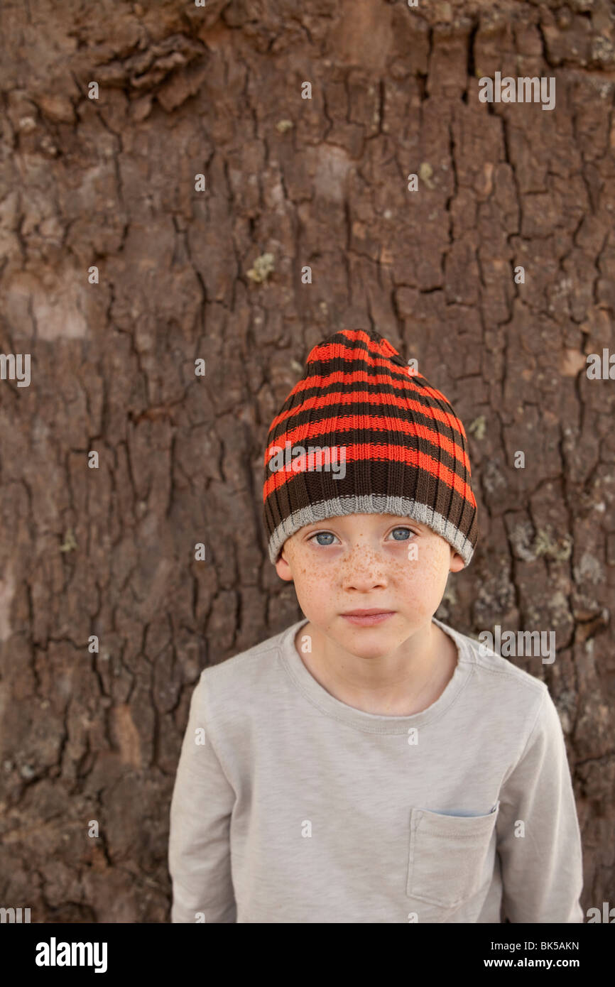 Freckled boy in striped beanie - Stock Image