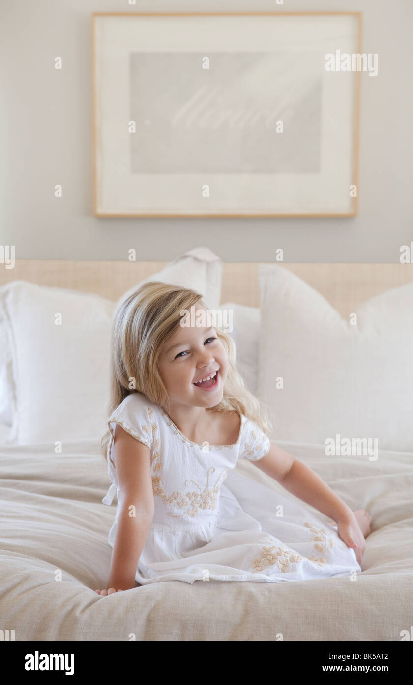 Girl with big smile sitting on bed - Stock Image