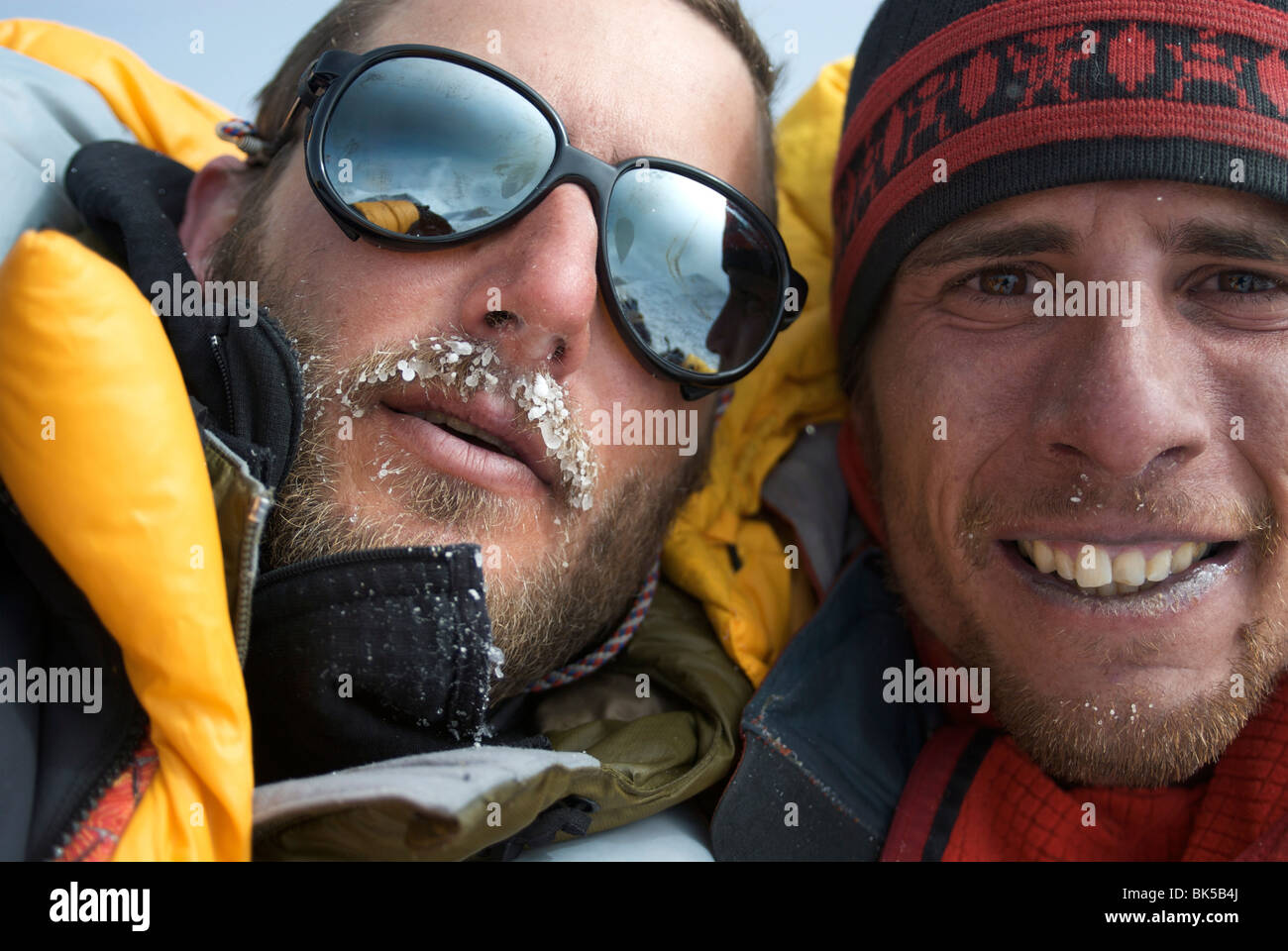 Two 30 year old men embrace on the summit of Mount Denali, Alaska, United States of America, North America - Stock Image