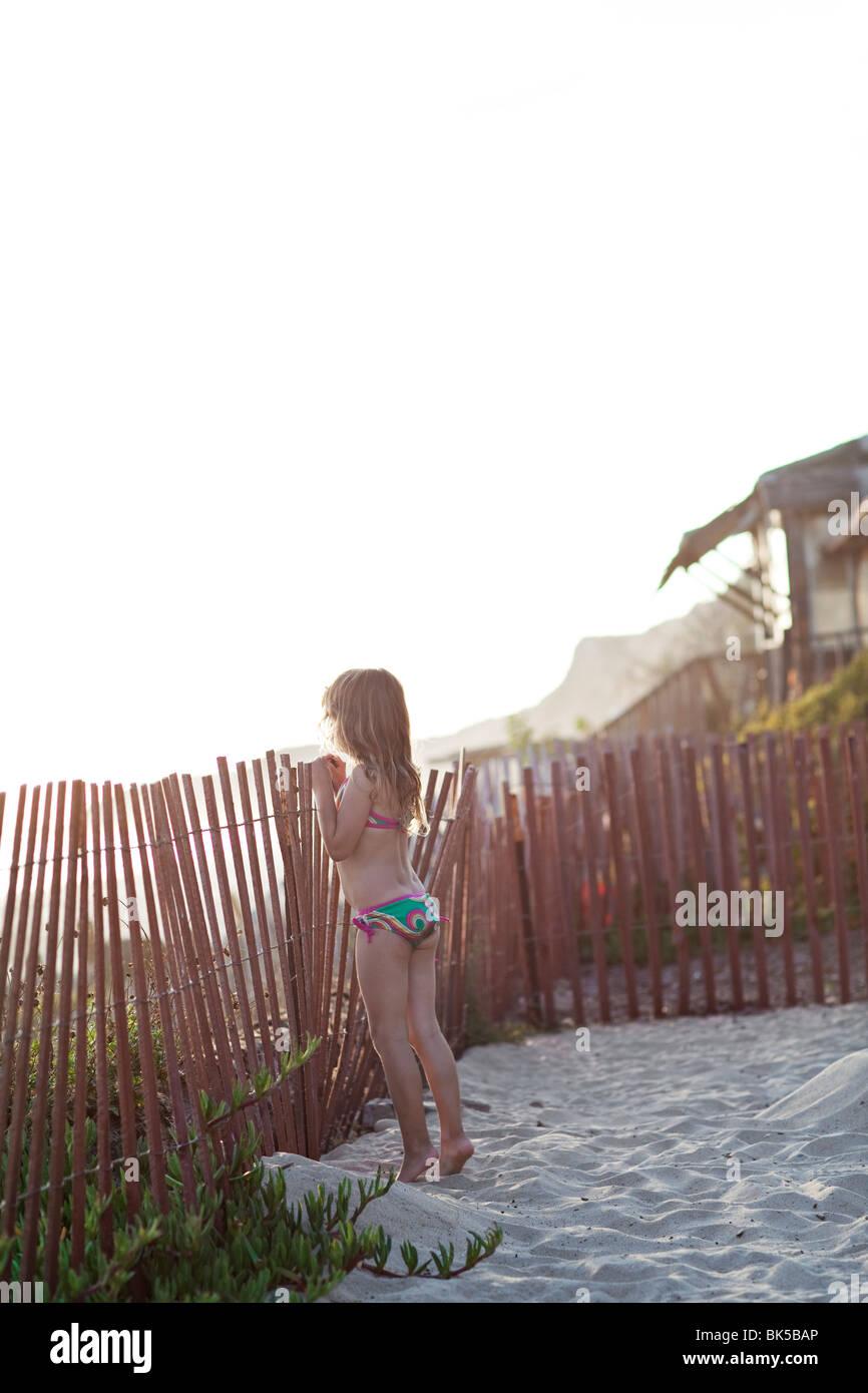 Girl in bikini peeking over fence at the beach - Stock Image