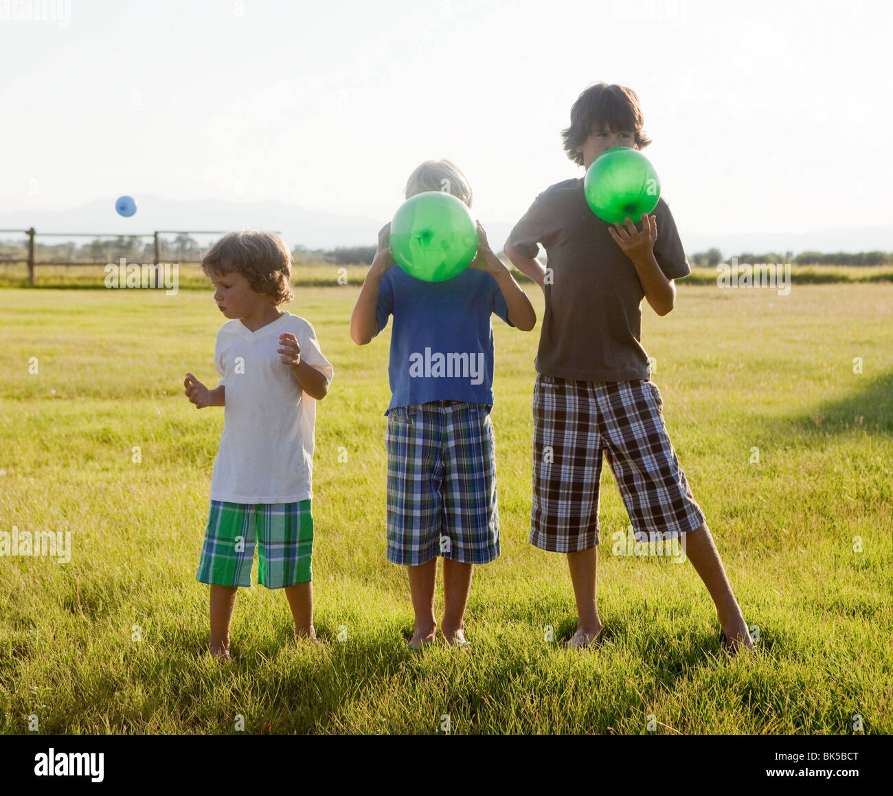 Boys blowing up balloons - Stock Image