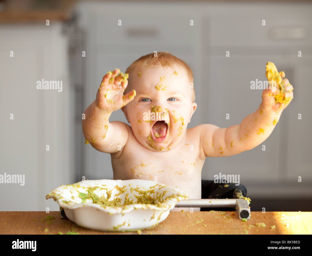 Happy baby playing in bowl of peas - Stock Image