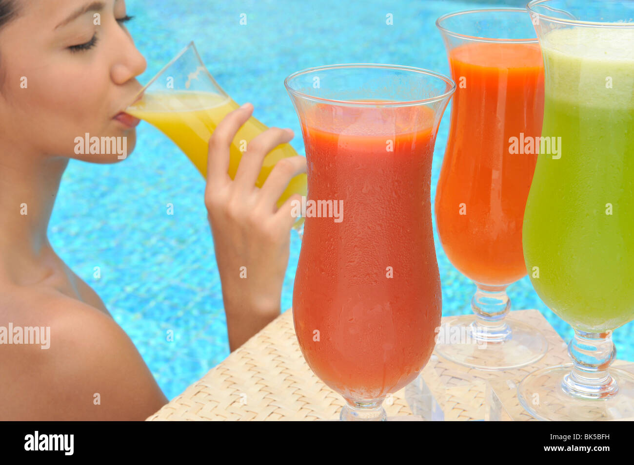 Young woman in a swimming pool sipping one of a selection of fruit juices - Stock Image