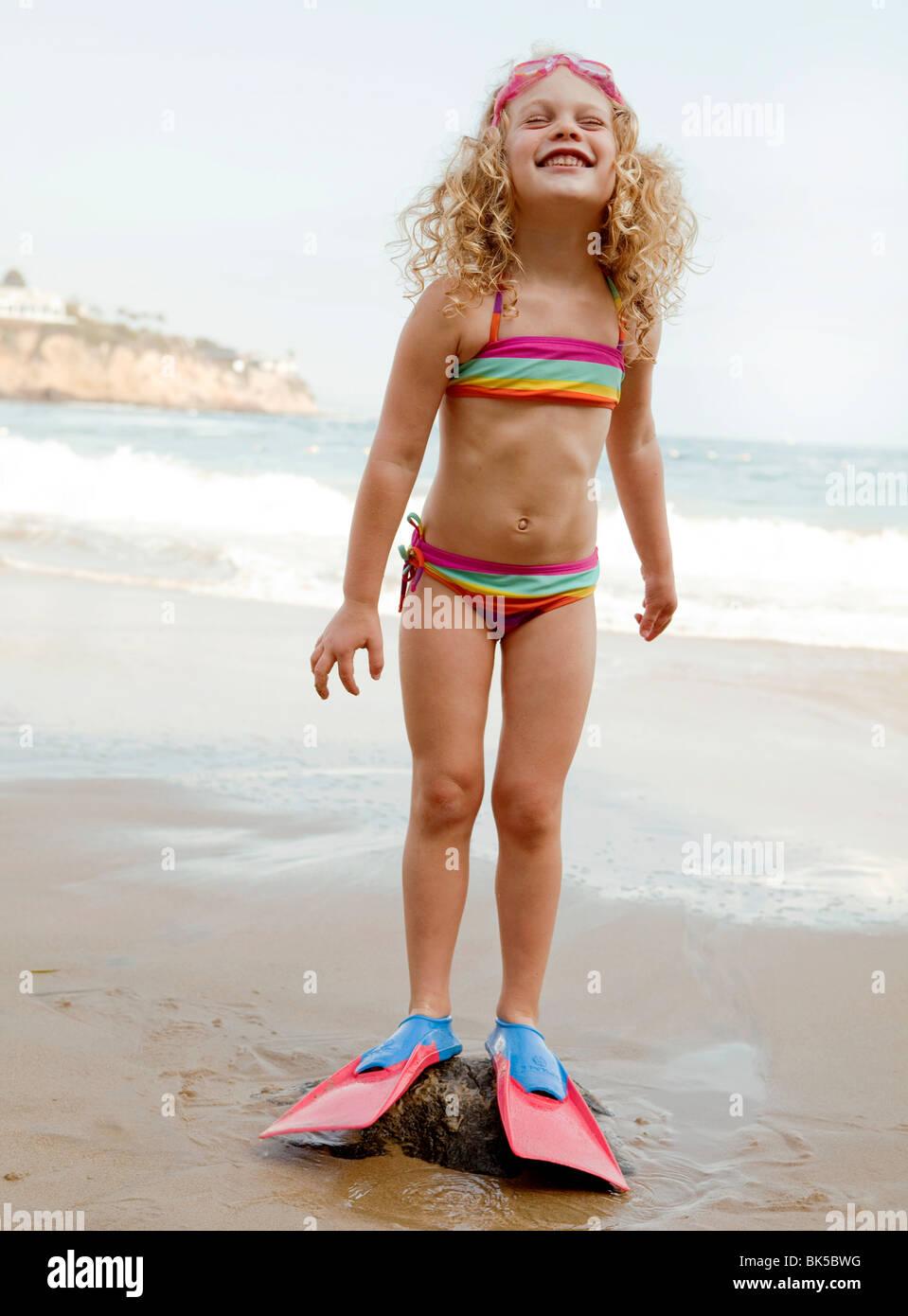 Girl in striped bikini and flippers at beach - Stock Image