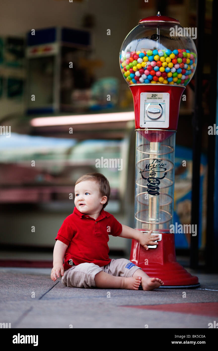 Young boy sitting by large gumball machine - Stock Image