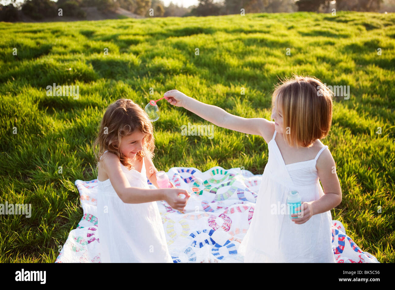 Girls on picnic blanket playing with bubbles - Stock Image