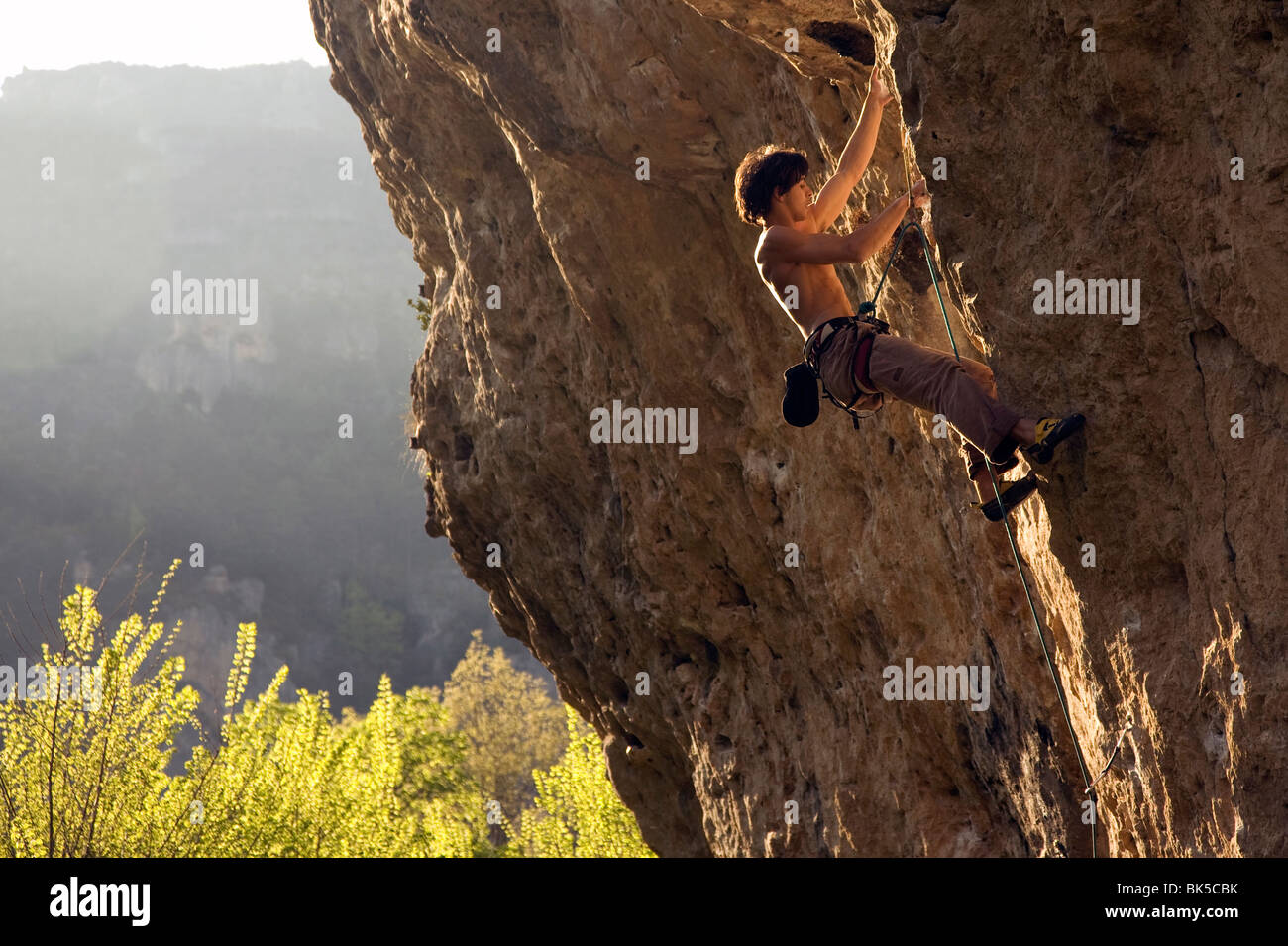 A climber tackles Dromadaire by the Tarn river, Gorges du Tarn, near Millau and Rodez, Massif Central, France - Stock Image