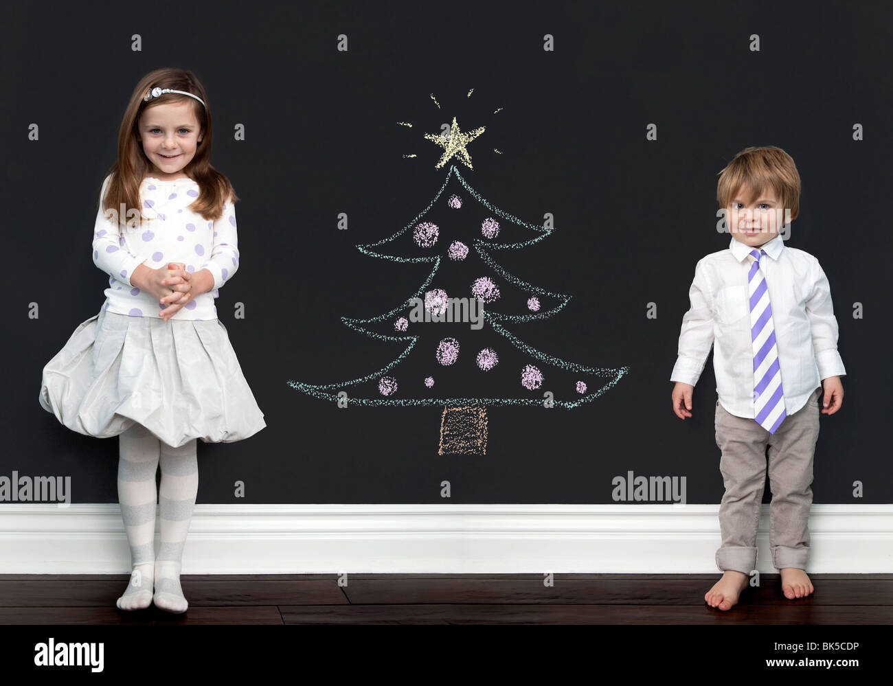 Brother and sister posing by imaginary christmas tree - Stock Image