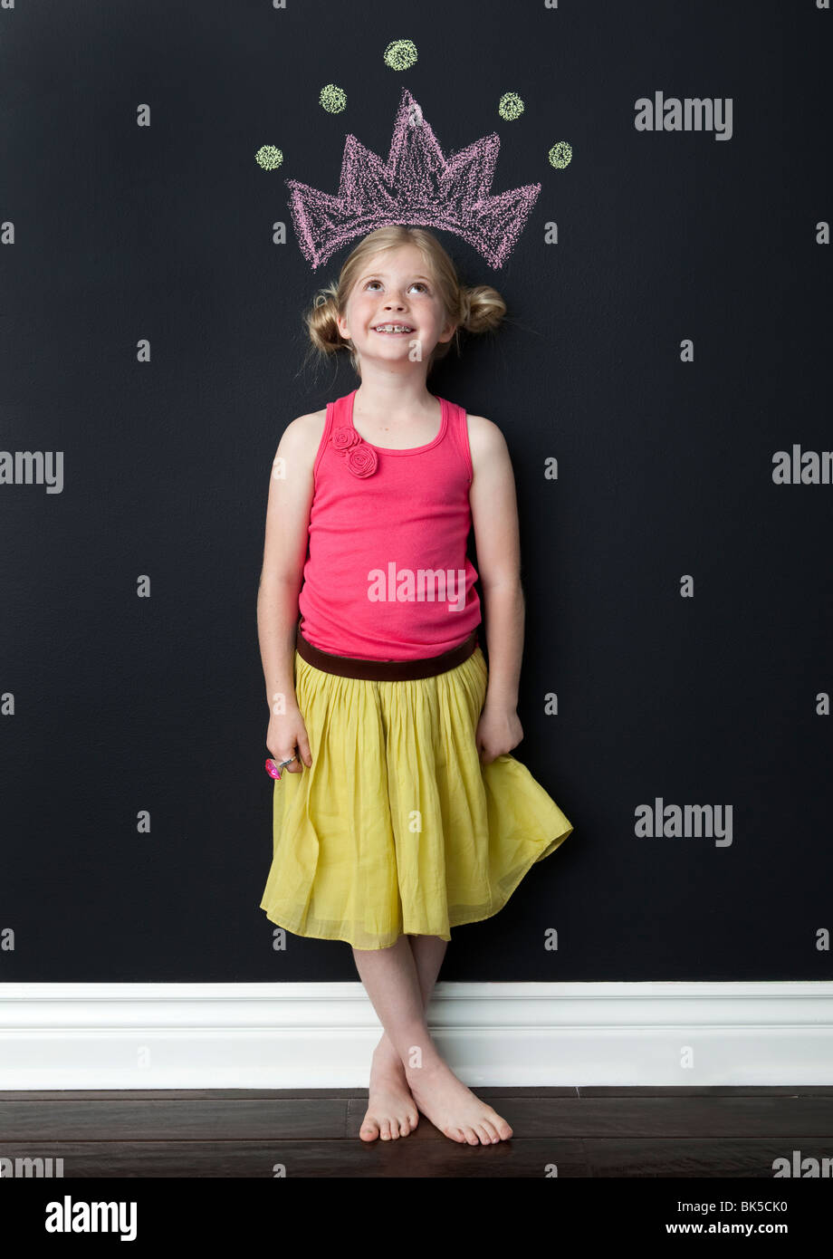 Girl posing beneath princess crown - Stock Image