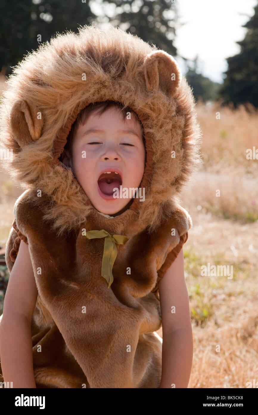 Yawning boy in lion costume - Stock Image