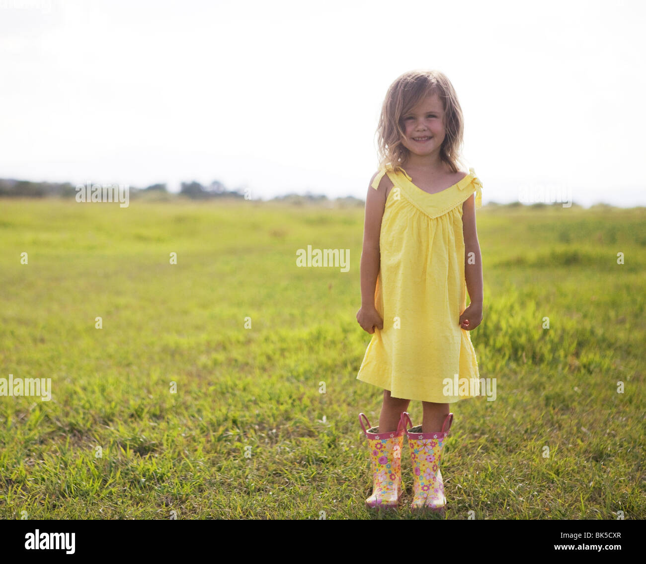 Young girl in yellow sundress and galoshes - Stock Image
