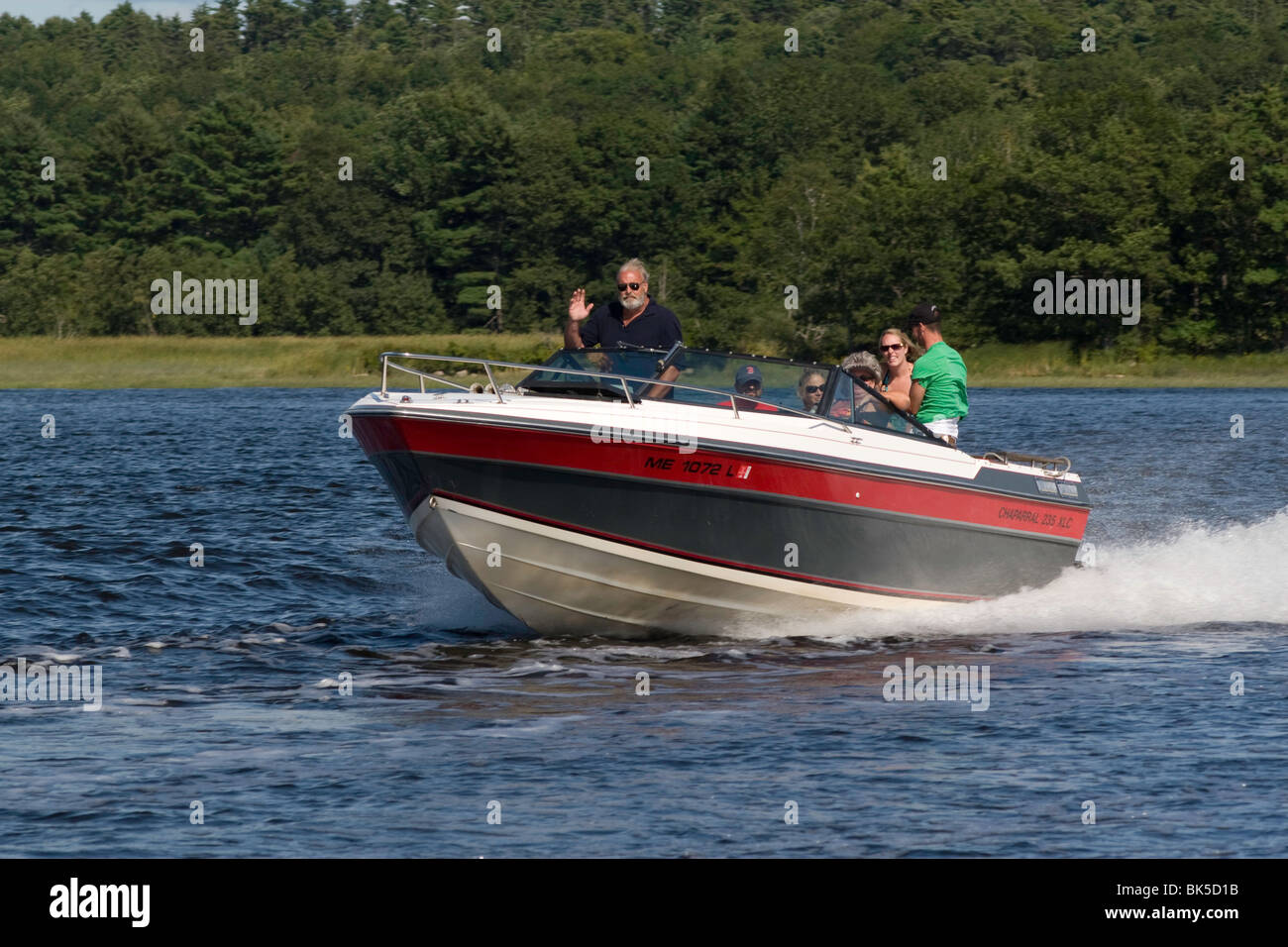 A speedy motorboat, friendly boaters, and a fine day for boating on the Sasanoa River, Maine - Stock Image