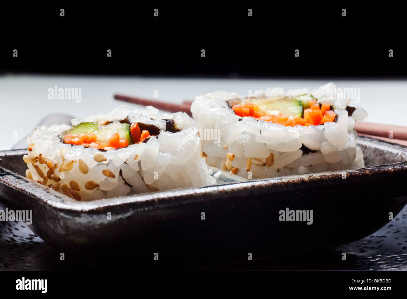 Vegetarian sushi California roll with rice and seaweed on Japanese plates - Stock Image