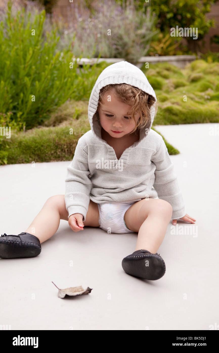 Toddler girl in gray sweatshirt sitting on sidewalk - Stock Image