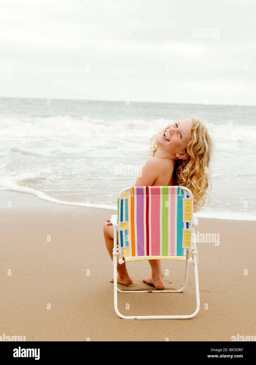 Young girl sitting on a beach chair at the beach - Stock Image