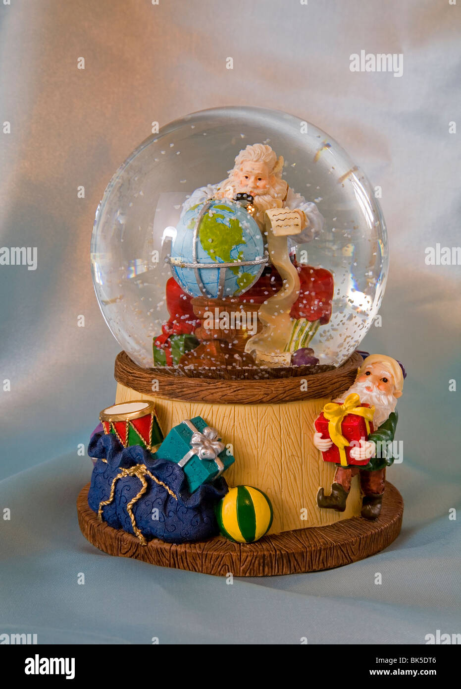 A snow globe featuring santa claus with a globe. - Stock Image