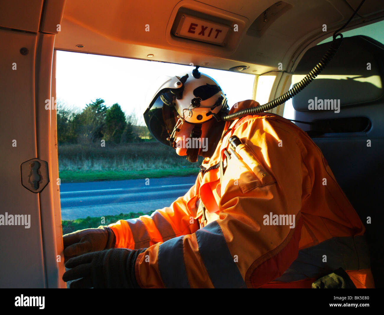 Air Ambulance Paramedic looking out of helicopter side doors during landing on the scene of a car accident - Stock Image