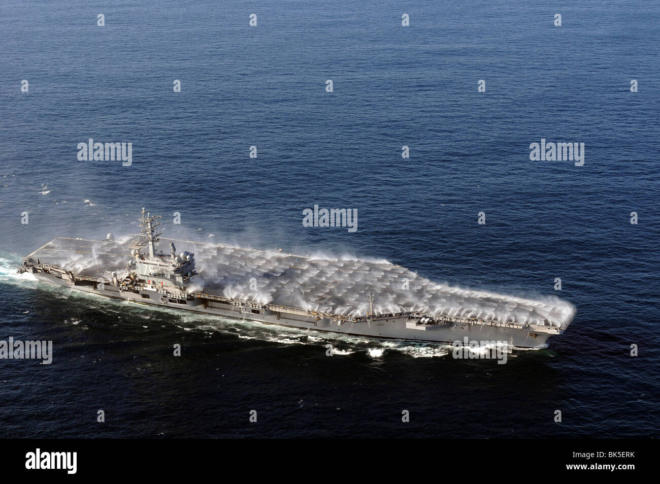 Countermeasure wash down sprinklers are activated as the Nimitz-class aircraft carrier USS Ronald Reagan (CVN-76) - Stock Image