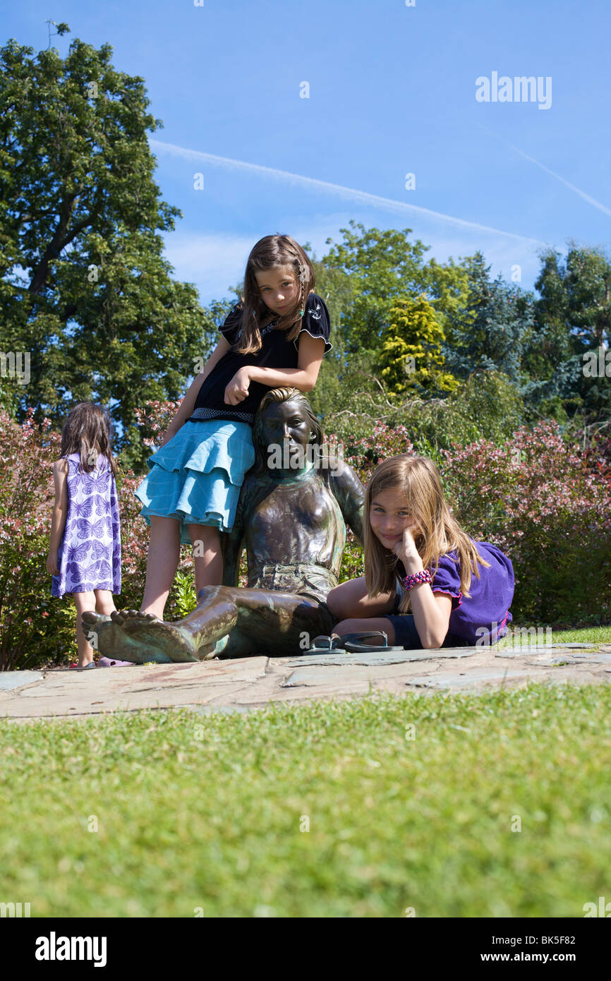 Children playing on statue, Golders Hill Park, bordering on Hampstead Heath, London, England, United Kingdom, Europe - Stock Image