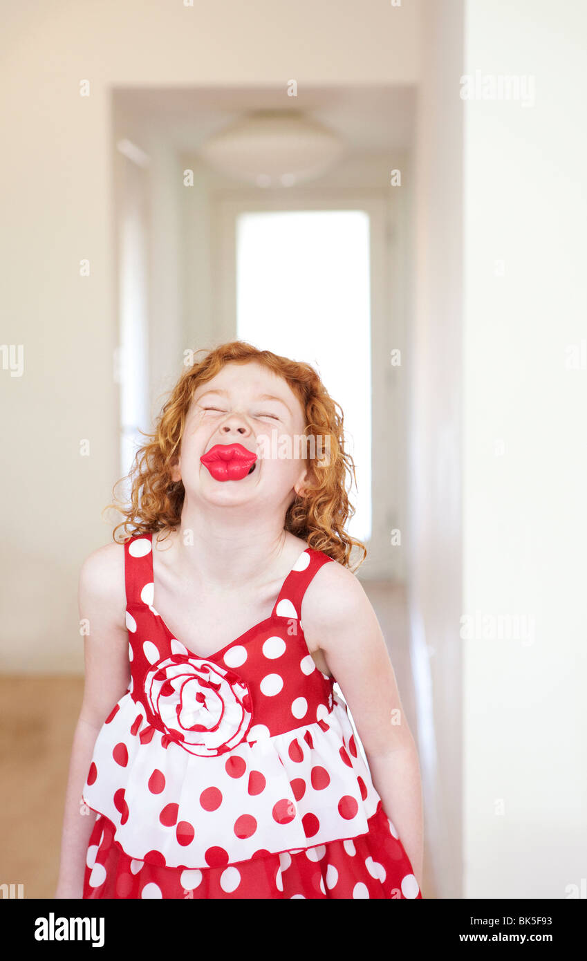 Girl in red and white polka dot dress with large lips - Stock Image