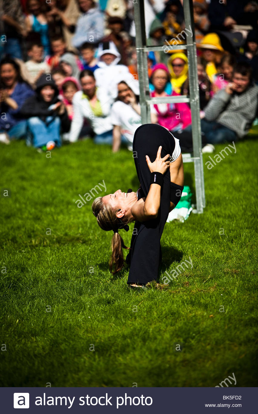 Contortionist  Bendy Em with crowd in background - Stock Image