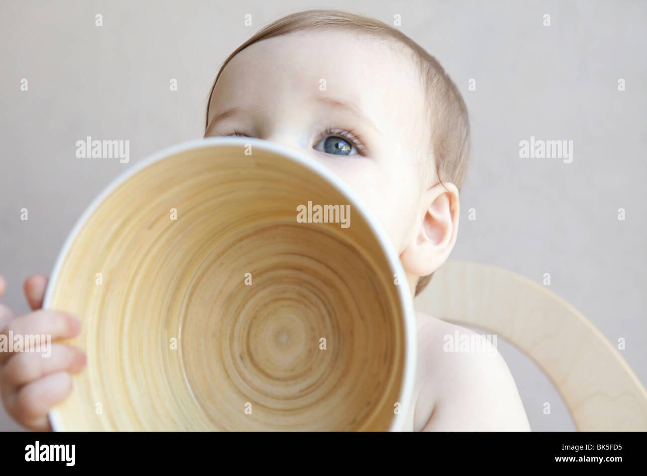 Baby holding large bowl - Stock Image