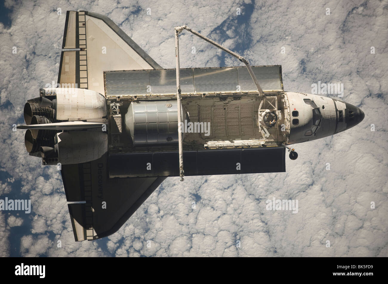 Backdropped by a cloud-covered part of Earth, Space Shuttle Discovery - Stock Image