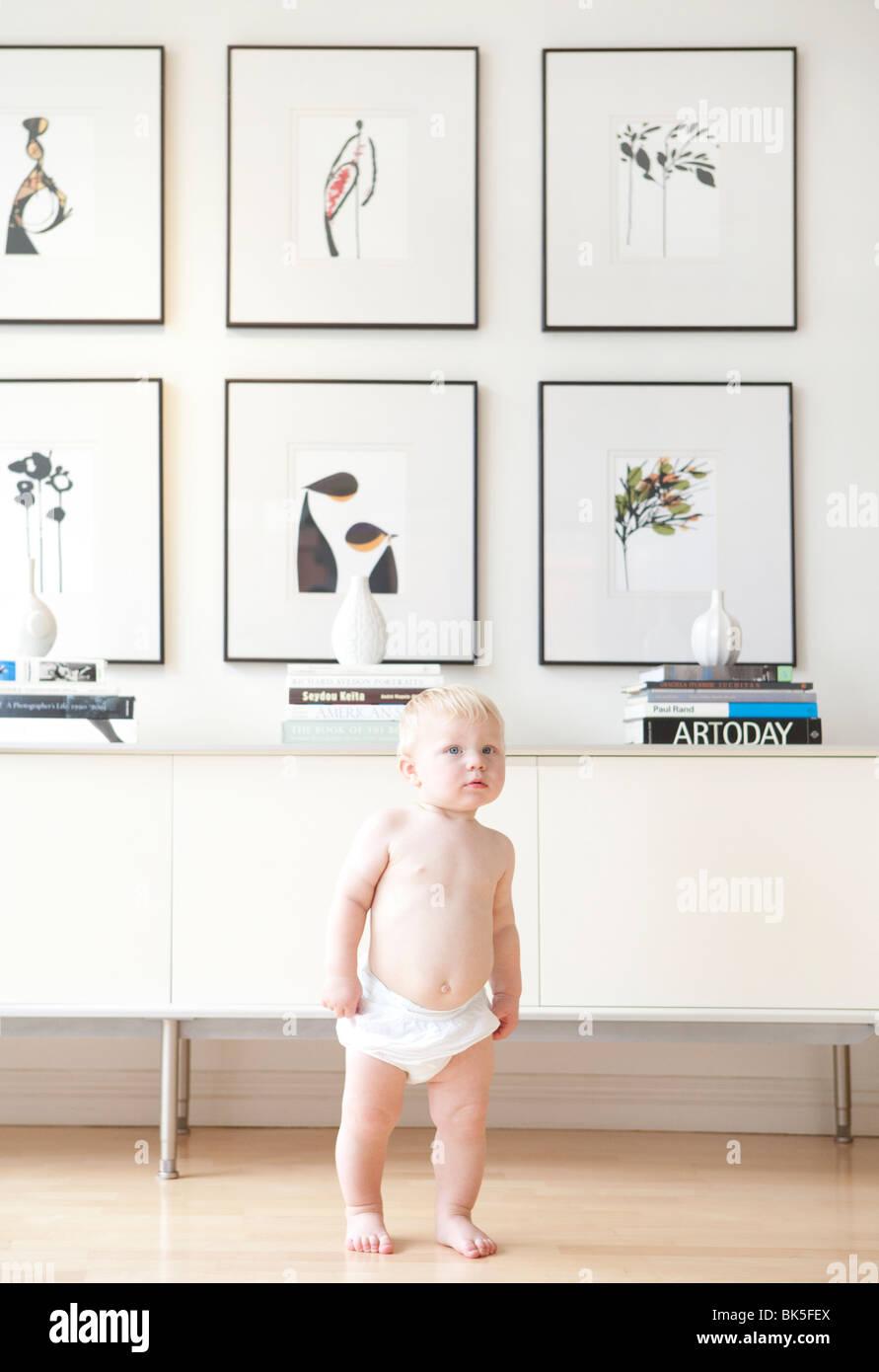 Baby in diaper in modern home - Stock Image